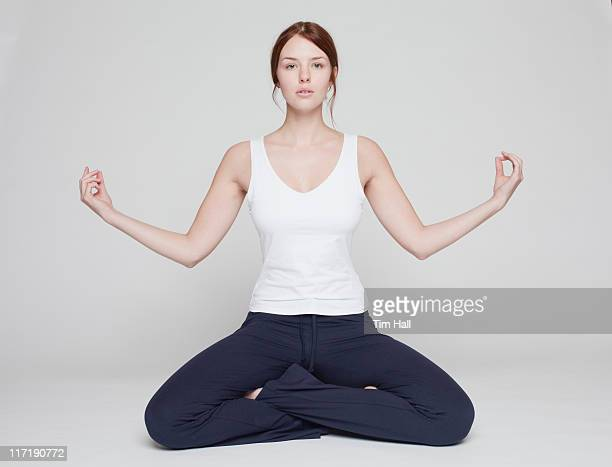 girl in lotus position on white background