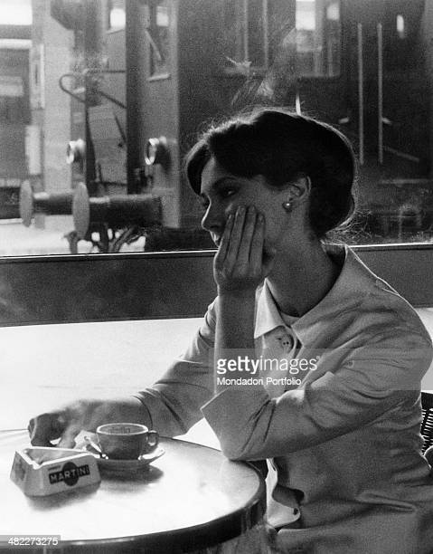 A girl in love sitting thoughtful at the table of a bar with a rail carriage behind her 1960s
