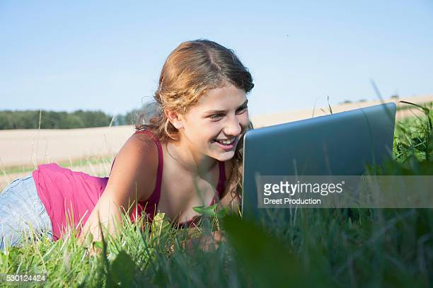 Girl (12-13) in meadow using laptop