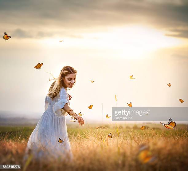 girl in meadow with flitting butterflies - schmetterling stock-fotos und bilder