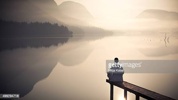 Girl in meditation by the lake