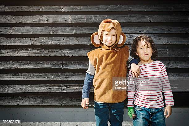 girl in monkey suit standing with friend against black wooden wall - monkey suit stock pictures, royalty-free photos & images