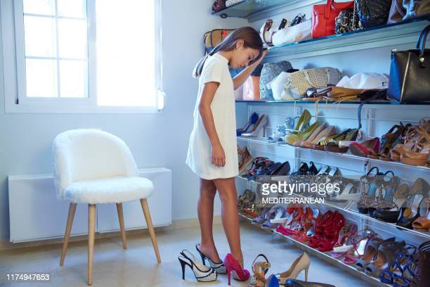 girl in mother wardrobe trying on shoes - extra long stock pictures, royalty-free photos & images
