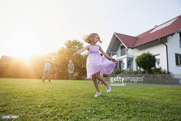 Girl in motion with family in garden