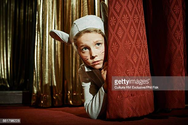 Girl in mouse costume behind stage curtain