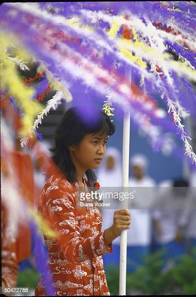 Girl in native print dress holding umbrella of feathers adding local color to festivities surrounding Nancy Reagan's visit