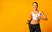 Girl In Oversize Jeans Gesturing Thumbs Up Smiling, Yellow Background