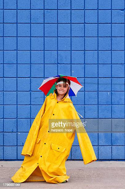 Girl in over-sized raincoat and umbrella hat