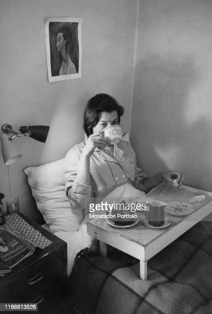 A girl in pajamas has breakfast in her bed on her legs a tray the photographer portrays her while she is raising a cup to her lips Milan 1956