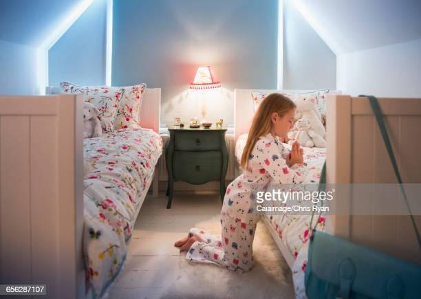 Girl in pajamas saying bedtime prayers at bed
