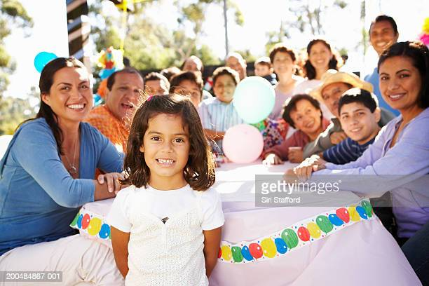 Girl (4-6) in park celebrating party with extended family