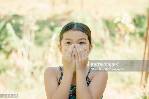 girl in park covering mouth with hands - filipino ethnicity and female not male fotografías e imágenes de stock