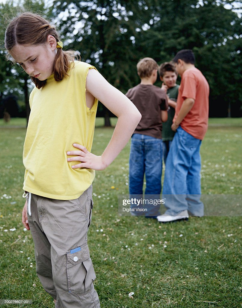 Girl (9-11) in park hand on hip, looking down, boys (9-12) in background : Stock Photo