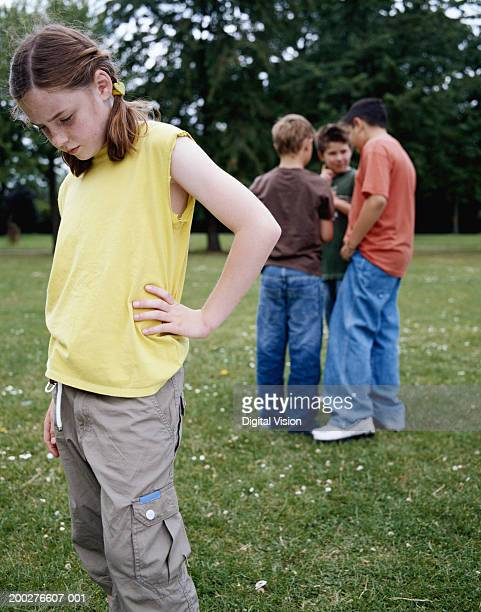 girl (9-11) in park hand on hip, looking down, boys (9-12) in background - nasty little girls stock photos and pictures