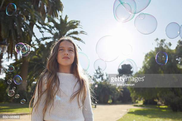 girl in park surrounded by bubbles looking away - surrounding stock pictures, royalty-free photos & images
