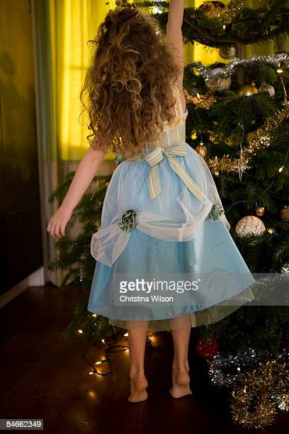 girl in party dress decorating xmas tree