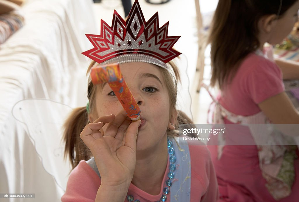 Girl (6-7) in party hat blowing party horn blower, elevated view : Foto de stock