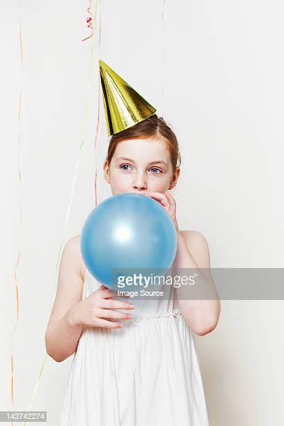 Girl in party hat, blowing up balloon