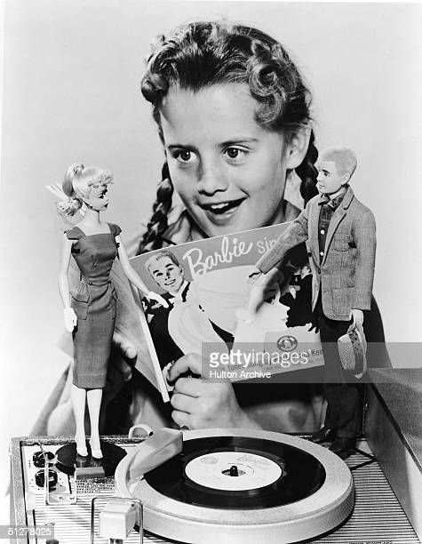 A girl in pigtails sings along with a 7 record called 'Barbie Sings' which plays on a portable phonograph player 1961 Two dolls Barbie and Ken stand...