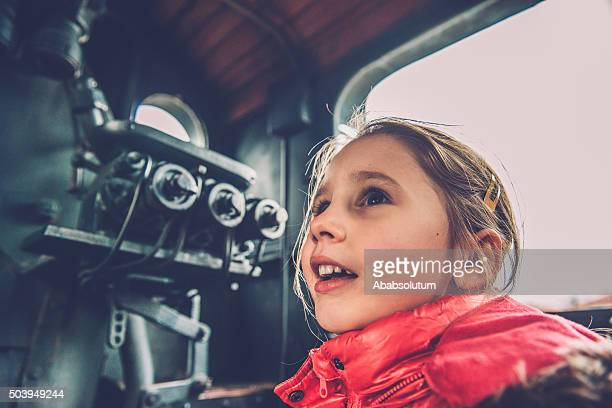 girl in pink admiring old steam locomotive, europe - locomotive stock photos and pictures