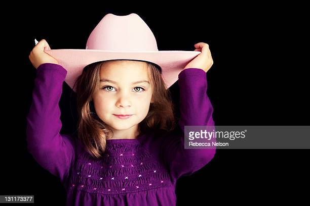 Girl in pink cowgirl hat on black background