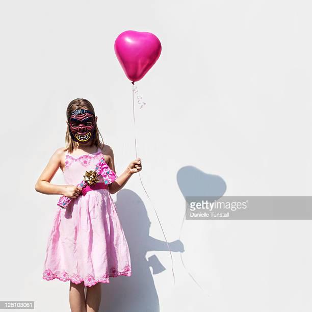 Girl in pink dress holding heart shape balloon