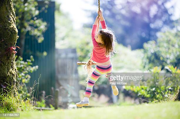 Girl in pink playing on swing