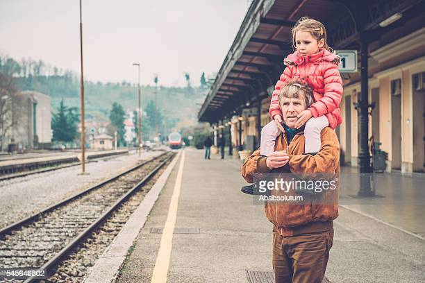 Girl in Pink Riding on Grandfather's Shoulder, Railway Station, Europe
