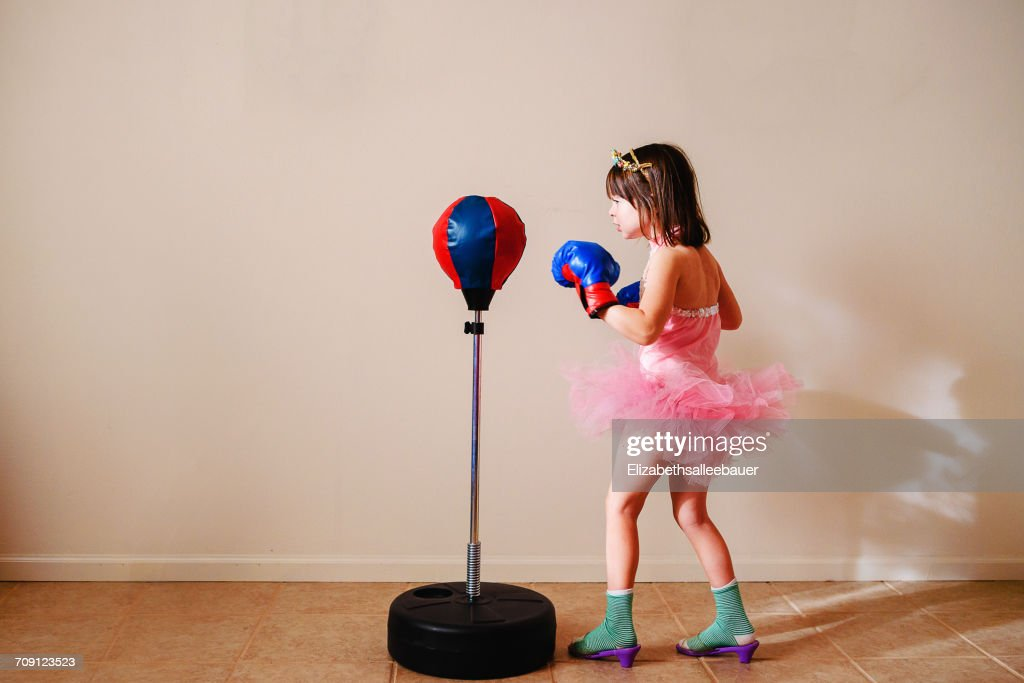 Girl in pink tutu and high heel shoes learning to box : Stock Photo