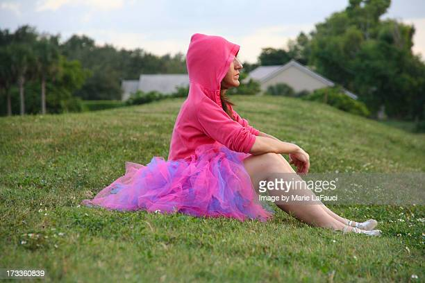girl in pink tutu hoodie sitting on green grass - marie lafauci stock pictures, royalty-free photos & images