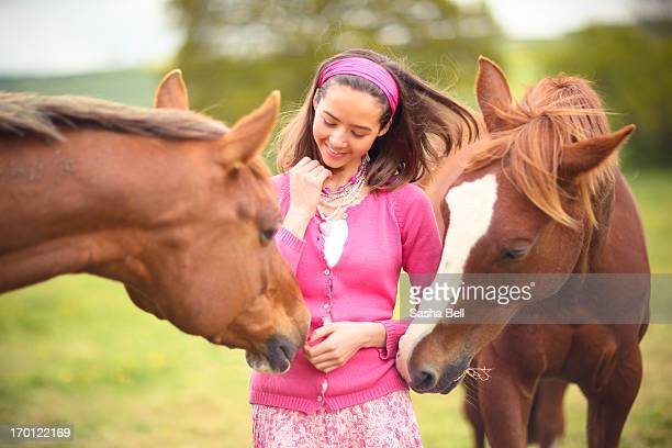 girl in pink with two chestnut horses - girl blowing horse - fotografias e filmes do acervo