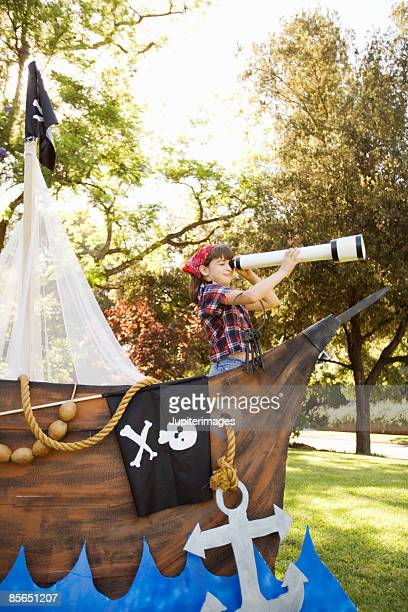 Girl in pirate costume playing on boat