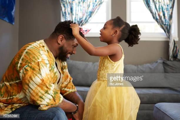 girl in princess costume putting tiara on father in living room - tiara stock-fotos und bilder