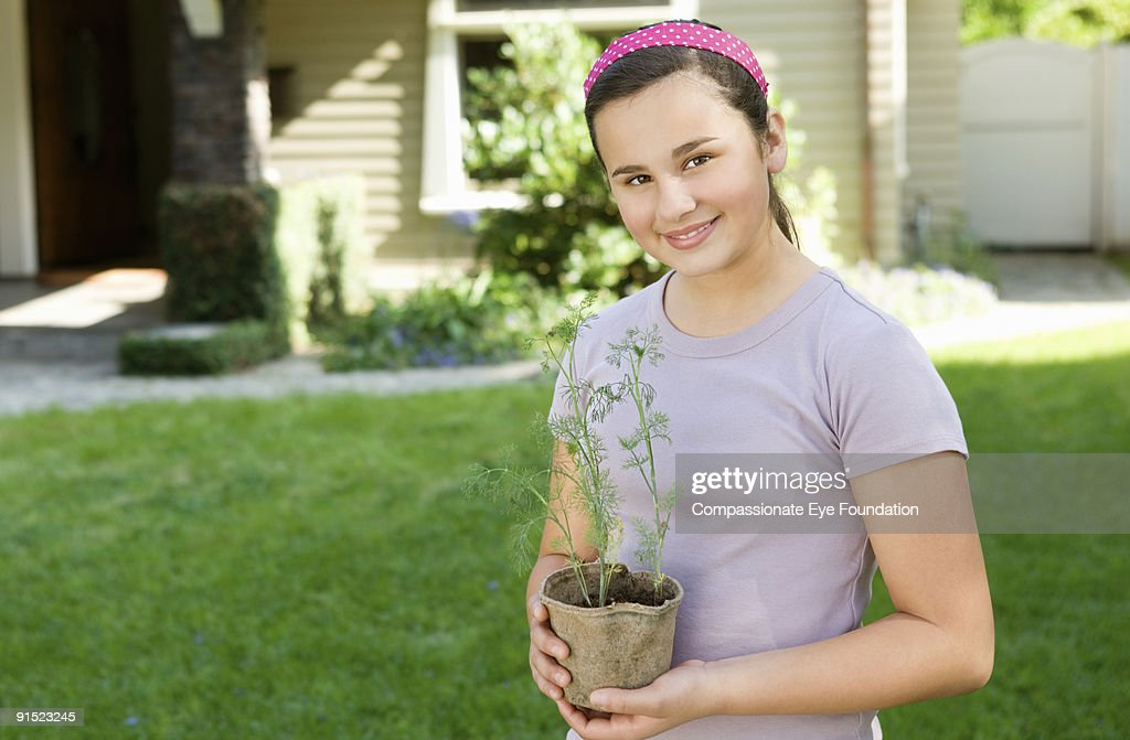 girl in purple tshirt holding a potted plant : Stock Photo