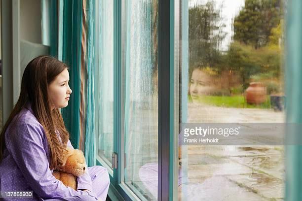 Girl in pyjamas looking out rainy window
