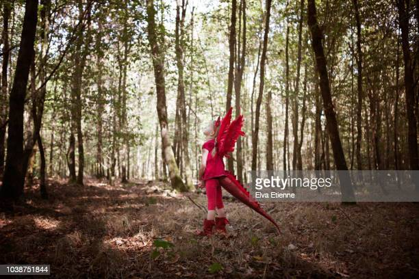 girl in red dragon costume daydreaming in a forest - devil costume stock photos and pictures