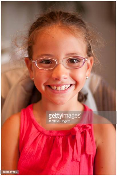 Girl in red dress and glasses smiling