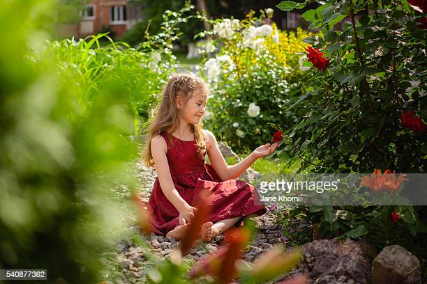 Girl in red dress touching red roses