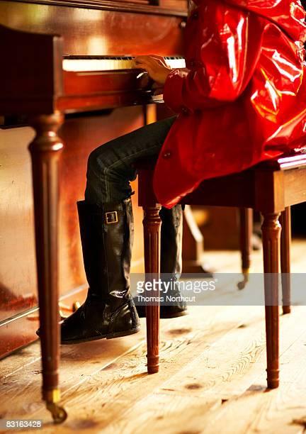 chica de rojo tocando el piano gabardina - gabardina ropa impermeable fotografías e imágenes de stock