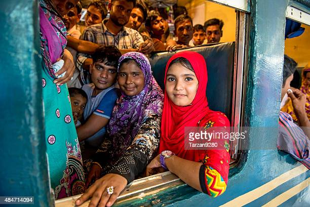 Girl in red sitting in crowded compartment, Dhaka, Bangladesh