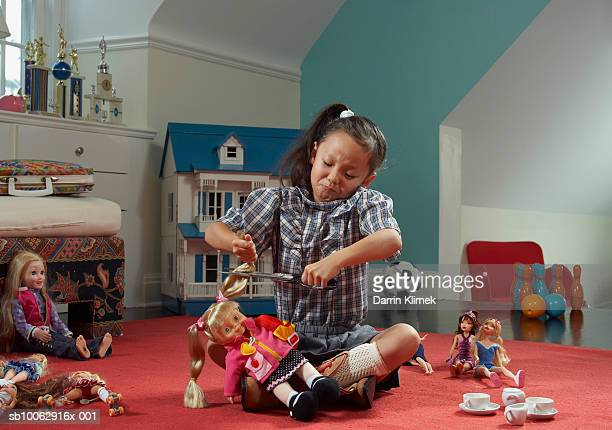 Girl (6-7 years) in room, cutting doll's hair