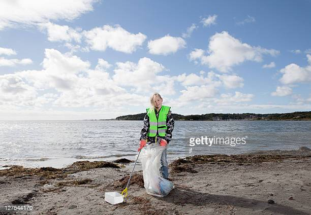Fille en veste de sécurité nettoyage de la plage