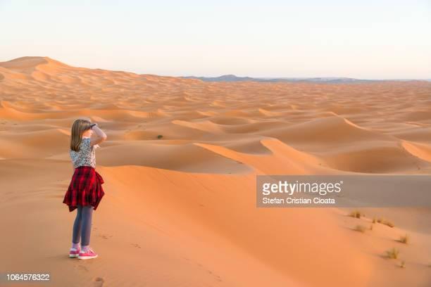 Girl in Sahara desert at sunset Morocco