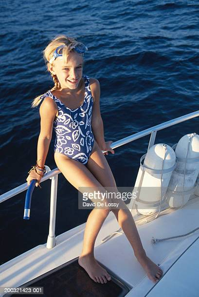 Girl (6-7) in sailboat, smiling, elevated view, portrait