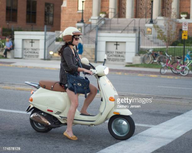 Girl in sandals on scooter waits at traffic light in front of a church