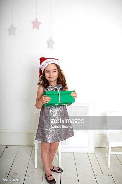 Girl in santa hat carrying Christmas gift