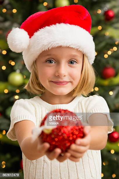 Girl (6-7) in Santa hat holding Christmas bauble