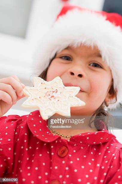 Girl (4-5) in Santa hat holding Christmas biscuit, smiling, close up
