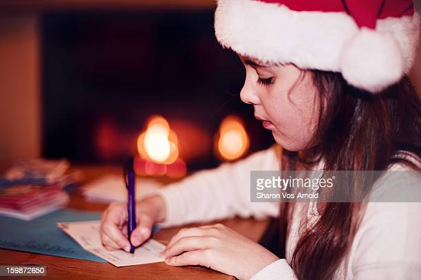 Girl in Santa hat writing christmas cards by fire
