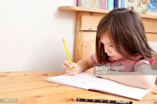 girl (6-7) in school uniform writing in book